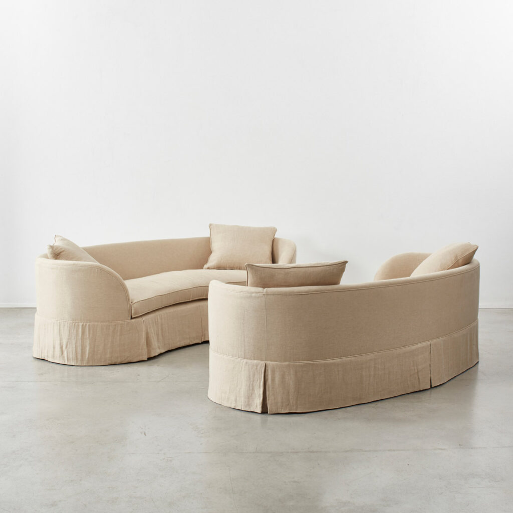 Pair of curved banana skirted sofas